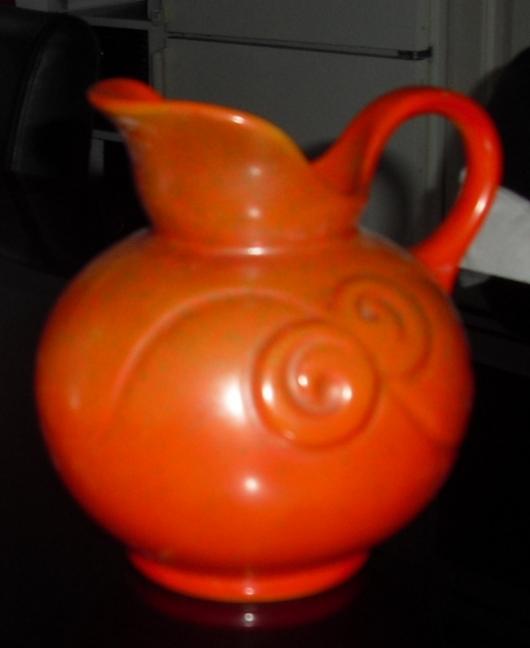Oranje kan met sierlijke krullen